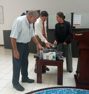 Chairperson of the Association Jamshed Pardiwall,  Indian High Commissioner Suhag, and Chief Justice Mathilda Twomey examining some of the medical equipment